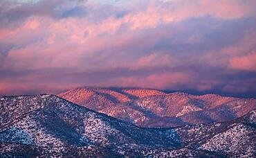 USA, New Mexico, Santa Fe, Colorful clouds at sunset over Sangre de Cristo Mountains
