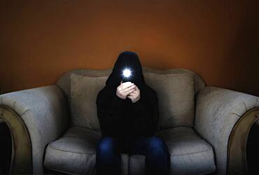 Man in hood sitting on sofa and holding flashlight in front of his face