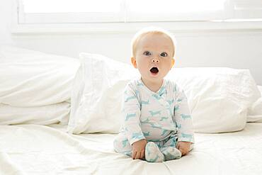 Baby boy with open mouth sitting on bed