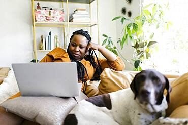 Woman lying on sofa with dog and working on laptop