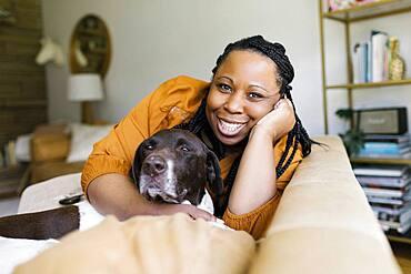 Smiling woman hugging dog on sofa