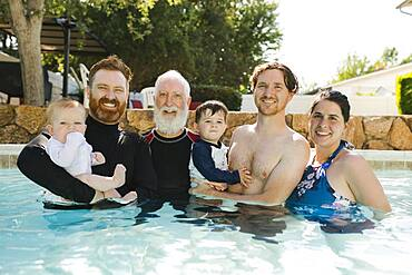 Portrait of family with boys (12-17 months, 2-3) in swimming pool - 1178-31719