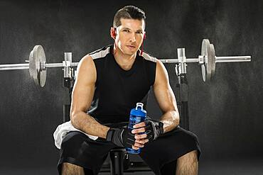 Muscular man training with barbell and holding water bottle
