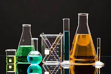 Laboratory glassware with liquids against black background