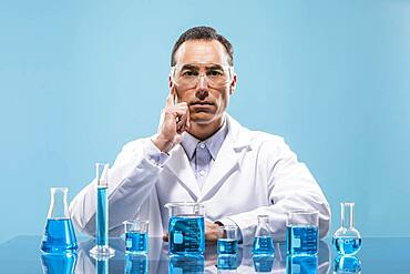 Portrait of scientist with beakers with blue liquid in foreground