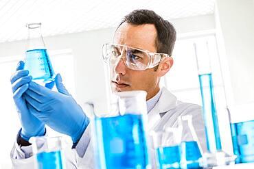 Scientist looking at blue liquid in laboratory