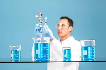 Scientist holding molecule model, blue liquid in beakers in foreground