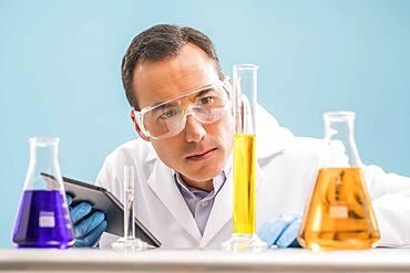 Scientist with digital tablet looking at yellow liquid in measuring beaker