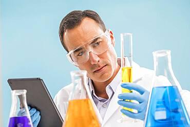 Scientist with digital tablet looking at yellow liquid in beaker