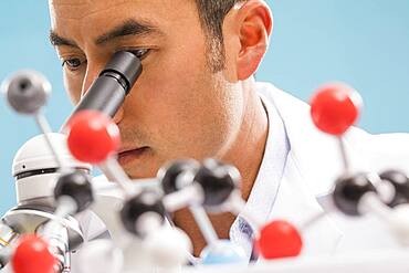 Close-up of scientist looking through microscope, molecular model in foreground
