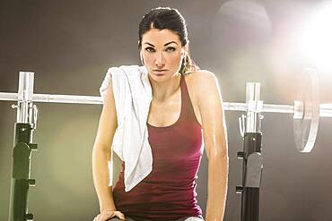 Studio portrait of woman in sleeveless top sitting at barbell
