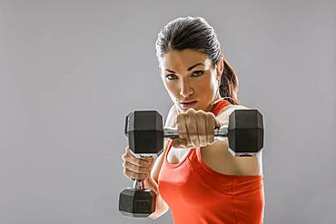 Studio portrait of athletic woman in red sleeveless top exercising with dumbbells