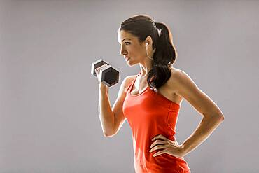 Studio shot of athletic woman in red sleeveless top exercising with dumbbell