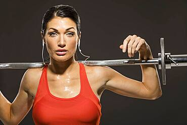 Studio portrait of athletic woman in red sleeveless top with barbell