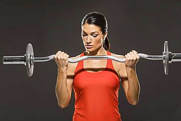 Athletic woman in red sleeveless top weight training