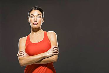 Studio portrait of athletic woman in red sleeveless top
