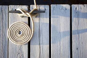 Overhead view of coiled rope tied around bollard