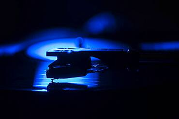 Close-up of a record player needle on record in blue light