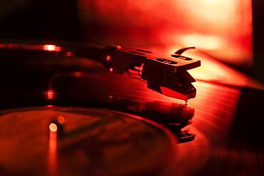 Close-up of a record player needle on record in red light
