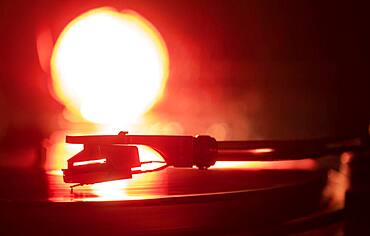 Close-up of a record player needle on record in orange light