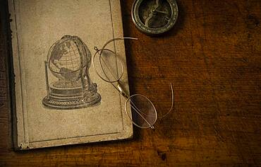 Old book resting on old wooden desk top with old eyeglasses and small sundial