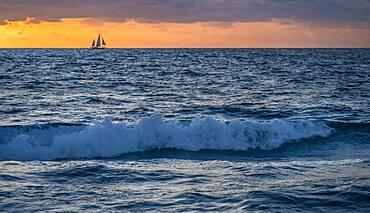 USA, Florida, Boca Raton, Sunrise over sea with silhouette of sailboat in distance