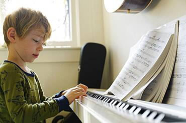 Boy (6-7) playing piano