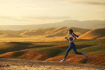 Woman jogging in landscape at sunset