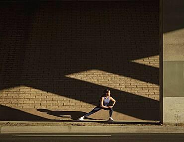 Woman stretching near brick wall in sunlight