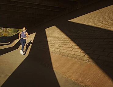 Woman jogging near brick wall in sunlight