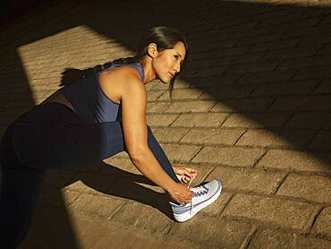 Athletic woman tying sport shoe outdoors