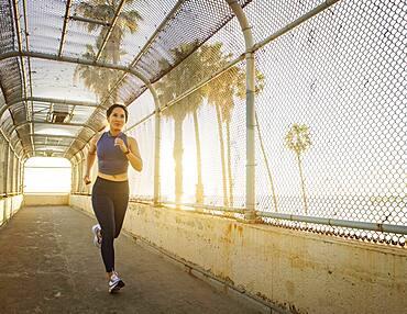 Woman jogging near beach at sunset