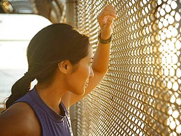 Athlete woman resting at fence