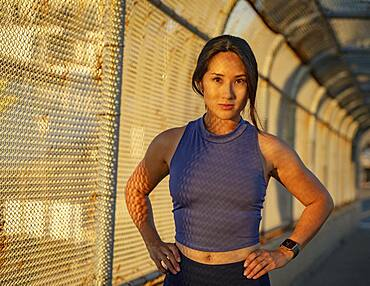 Portrait of athlete woman at fence