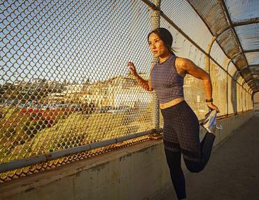 Athlete woman stretching at fence