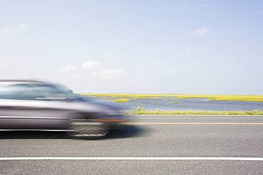 Virginia, Chincoteague, Car on road blurred in motion