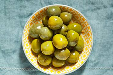 Overhead view of green olives in bowl