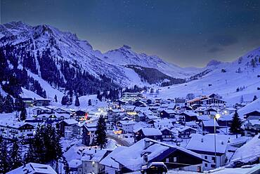 Italy, Dolomites, Alta Badia, Village covered with snow in mountain valley at dusk