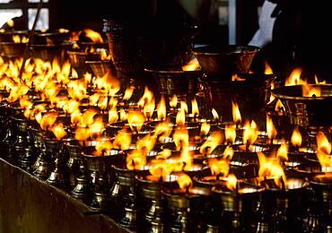 China, Tibet, Lhasa, Burning candles in Tibetan Buddhist temple