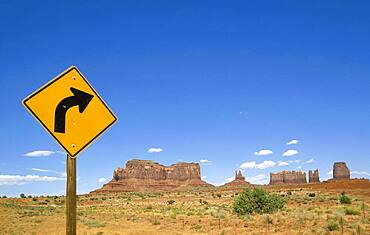 Arizona, Monument Valley Tribal Park, Road sign in Monument Valley with West and East Mitten Buttes in background