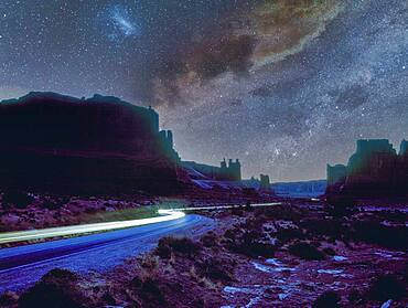 USA, Arizona, Monument Valley Tribal Park, Cars lights on dirt road in Monument Valley at night