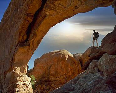 USA, Utah, Arches National Park, Climber under rocky arch at sunset
