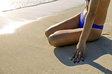 Woman in bikini sitting on beach, low section