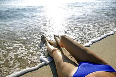 Woman in bikini lying on beach, low section