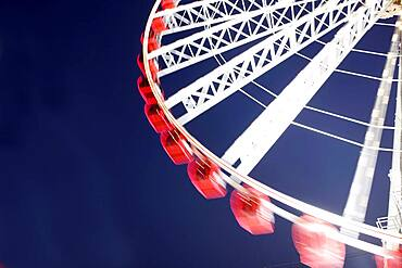 Low angle view of spinning ferris wheel