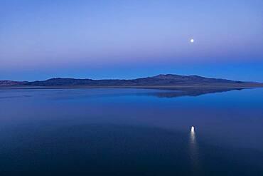 USA, Nevada, Hawthorne, Calm Walker Lake reflecting Moon at dusk