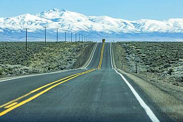 USA, Nevada, Winnemucca, Highway 95 crossing desert landscape with snowcapped mountains in distance