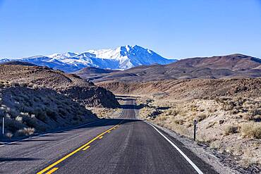 USA, California, Bishop, Highway 6 crossing desert landscape with snowcapped Sierra Nevada Mountains in distance
