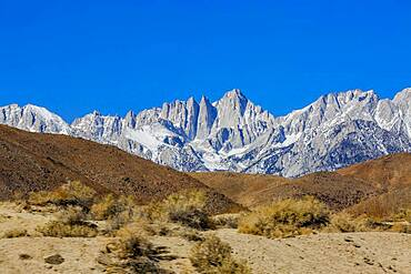 USA, California, Lone Pine, Snowcapped Mount Whitney with rocky hills in foreground