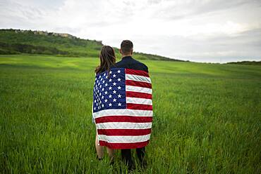 Rear view of young couple wrapped in American flag standing in wheat field